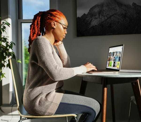 woman in gray sweater using Surface laptop